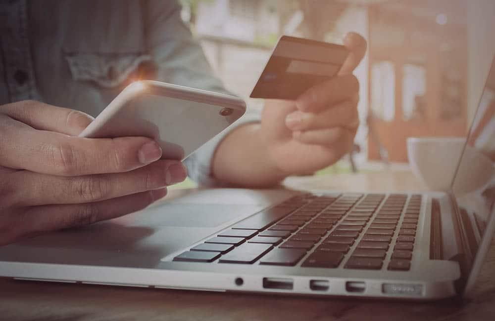 Um homem segura um celular e um cartão de crédito em cima de um notebook.