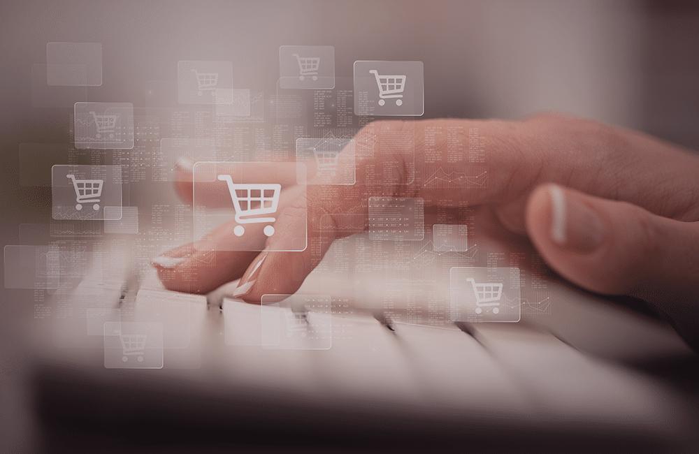 Uma mão digitando em um teclado com ícones de compras em cima