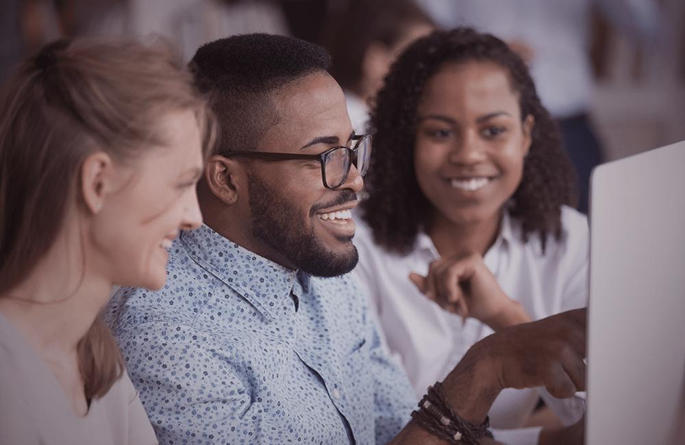 Um homem e duas mulheres sorrindo enquanto olham para um monitor