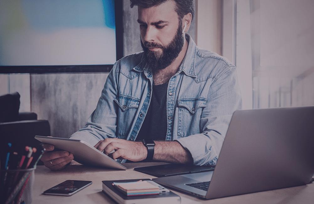 Homem em um escritório com um notebook e um tablet na mão
