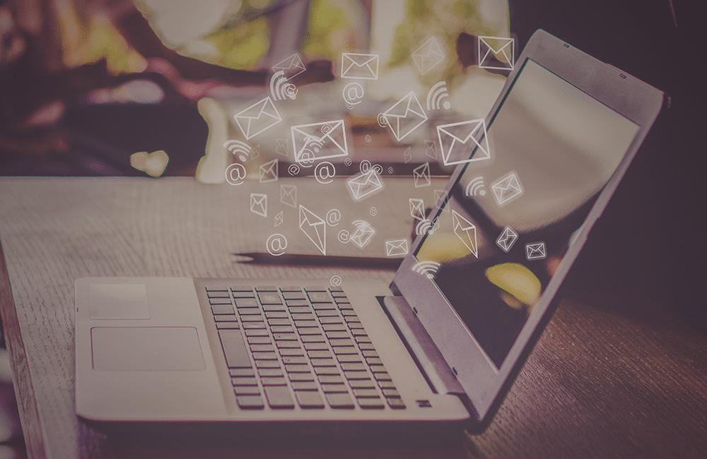 Um notebook aberto com ícones de e-mails e notificações saindo da sua tela