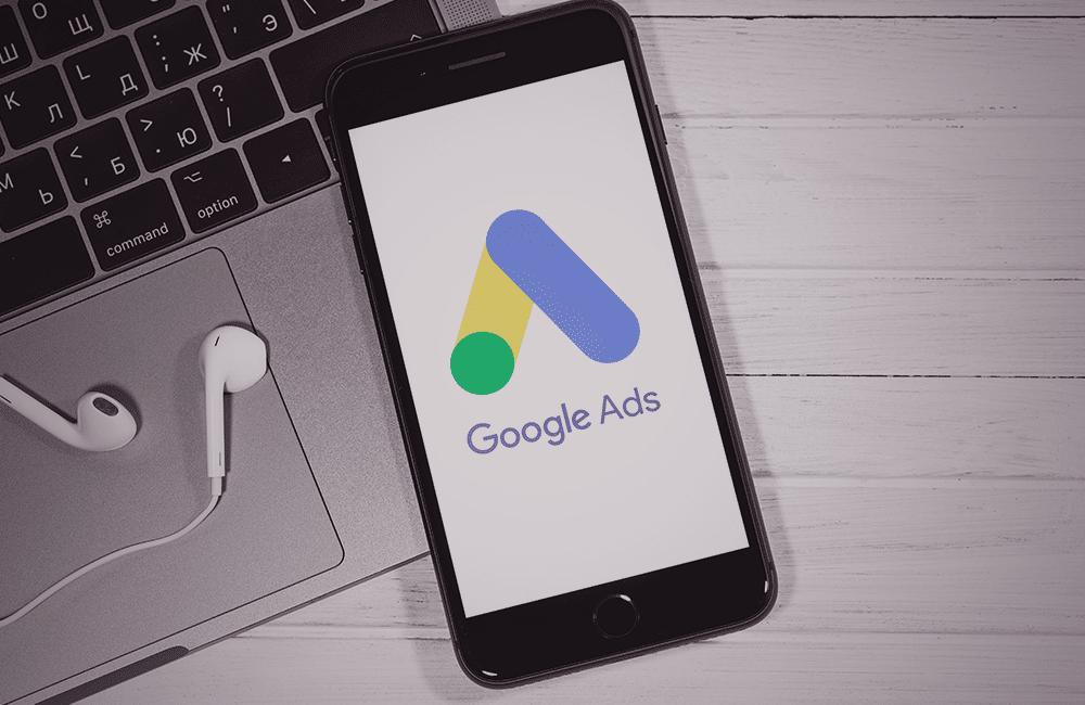 Celular apoiado em um notebook com o logo do Google Ads na tela