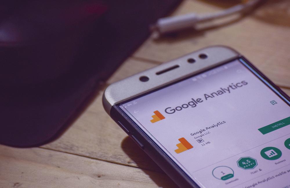 Um celular apoiado em uma mesa com a página de download do aplicativo do Google Analytics