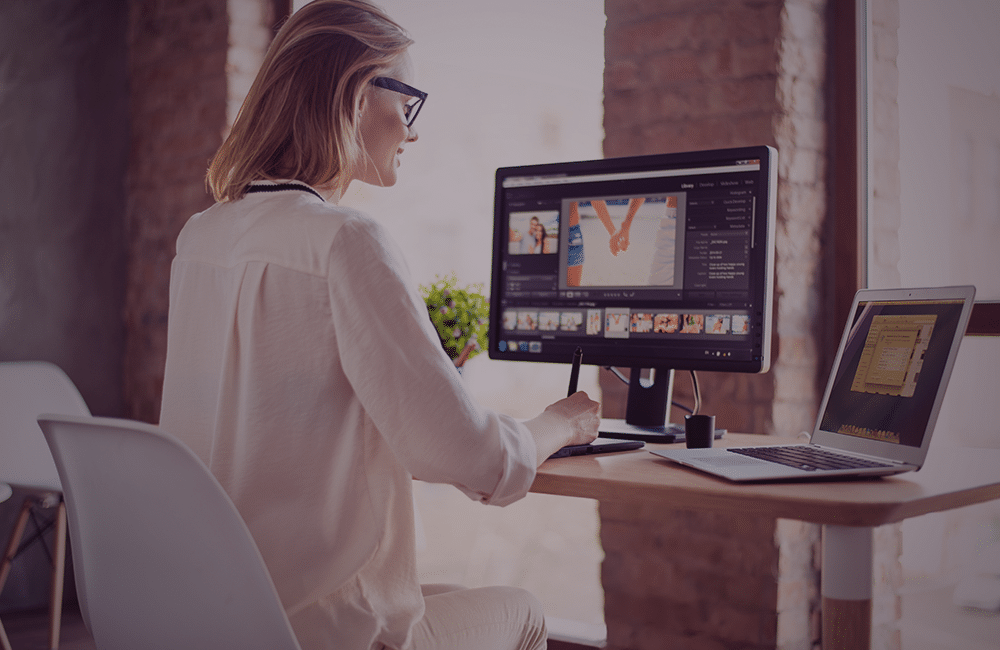 Mulher com um monitor e notebook mexendo em um software de edição