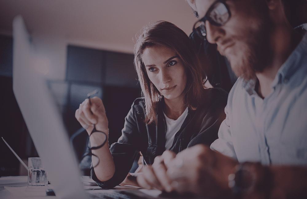 Um homem e uma mulher observando a tela de um notebook