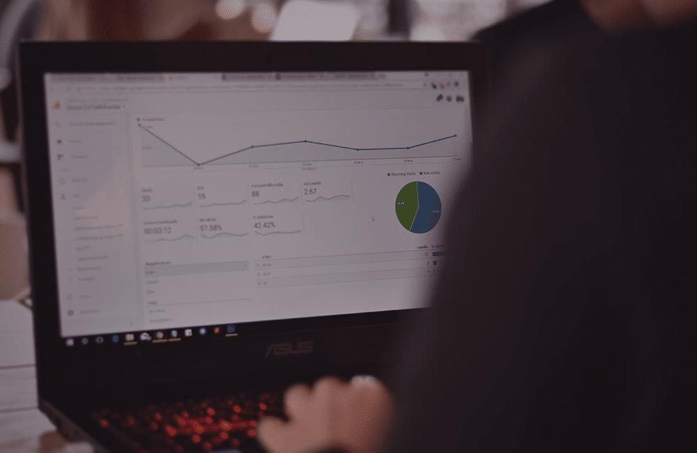 Uma pessoa de costas mexendo em um notebook com a página de gráficos do Google Analytics