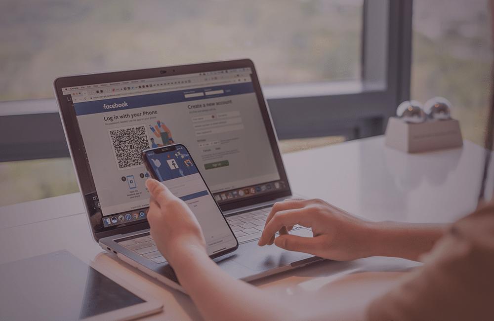 Uma pessoa mexendo em um celular e notebook, ambos conectados no Facebook